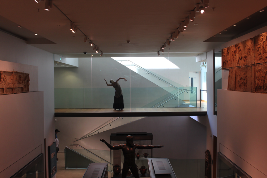 Photograph of Marie-Louise Crawley performing a solo, masked, dance piece at the Ashmolean Museum