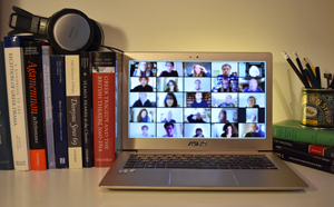 Photograph of laptop showing gallery view of online seminar, next to books and headphones