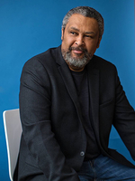 Photo of Kevin Willmott, seated, in front of a blue background