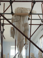 Photograph of an ancient Greek statue, without a head, surrounded by scaffolding
