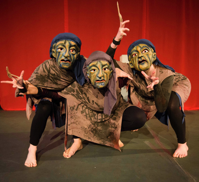 Three actors in theatrical masks, performing as Furies, crouching as a group in front of a red curtain