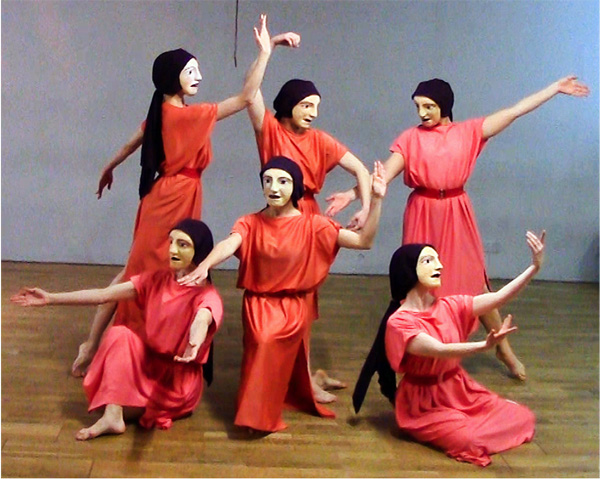 Six masked dancers in red robes perform a dance